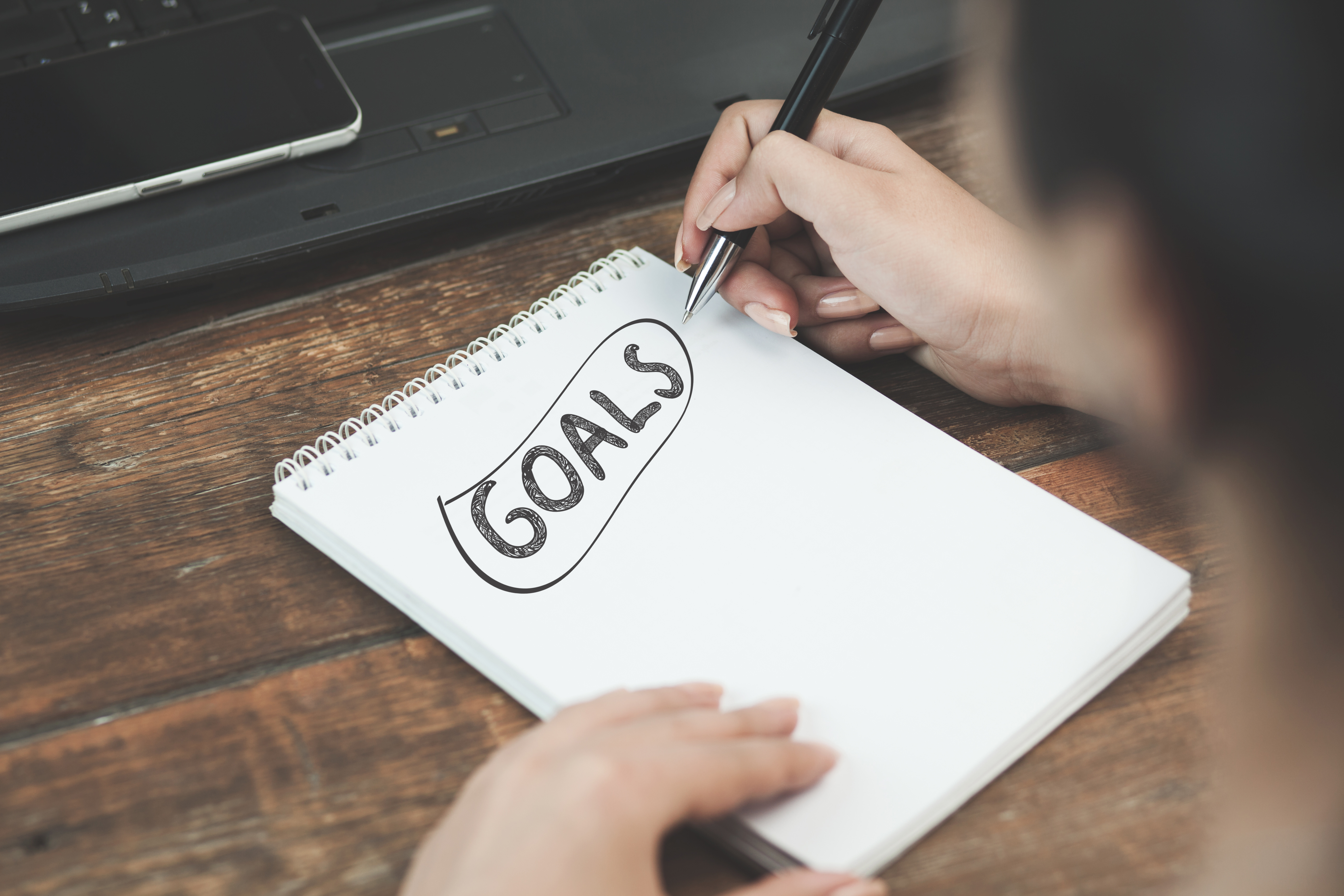 person writing down their goals on a notepad