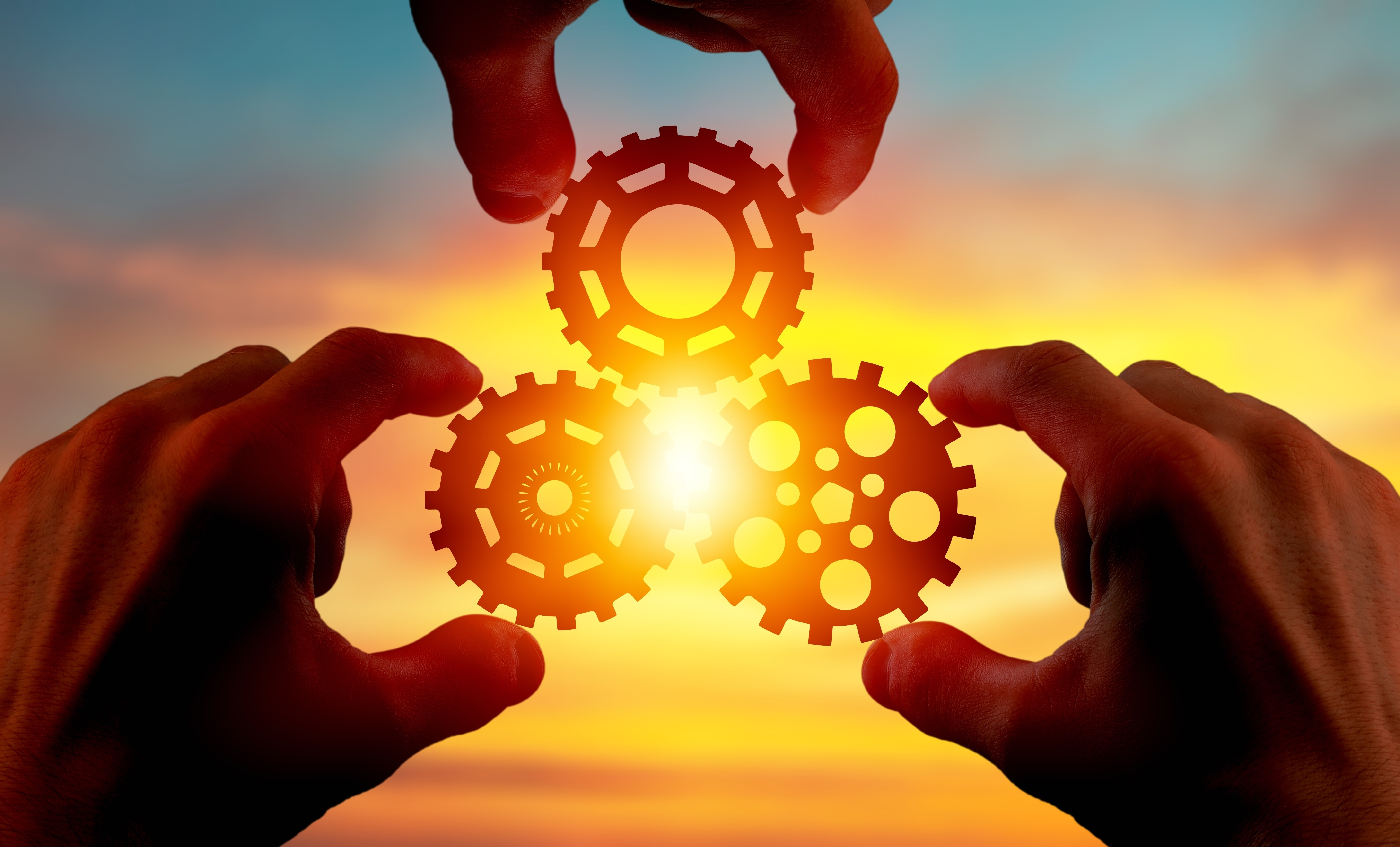 gears turning together with a sunset in the background