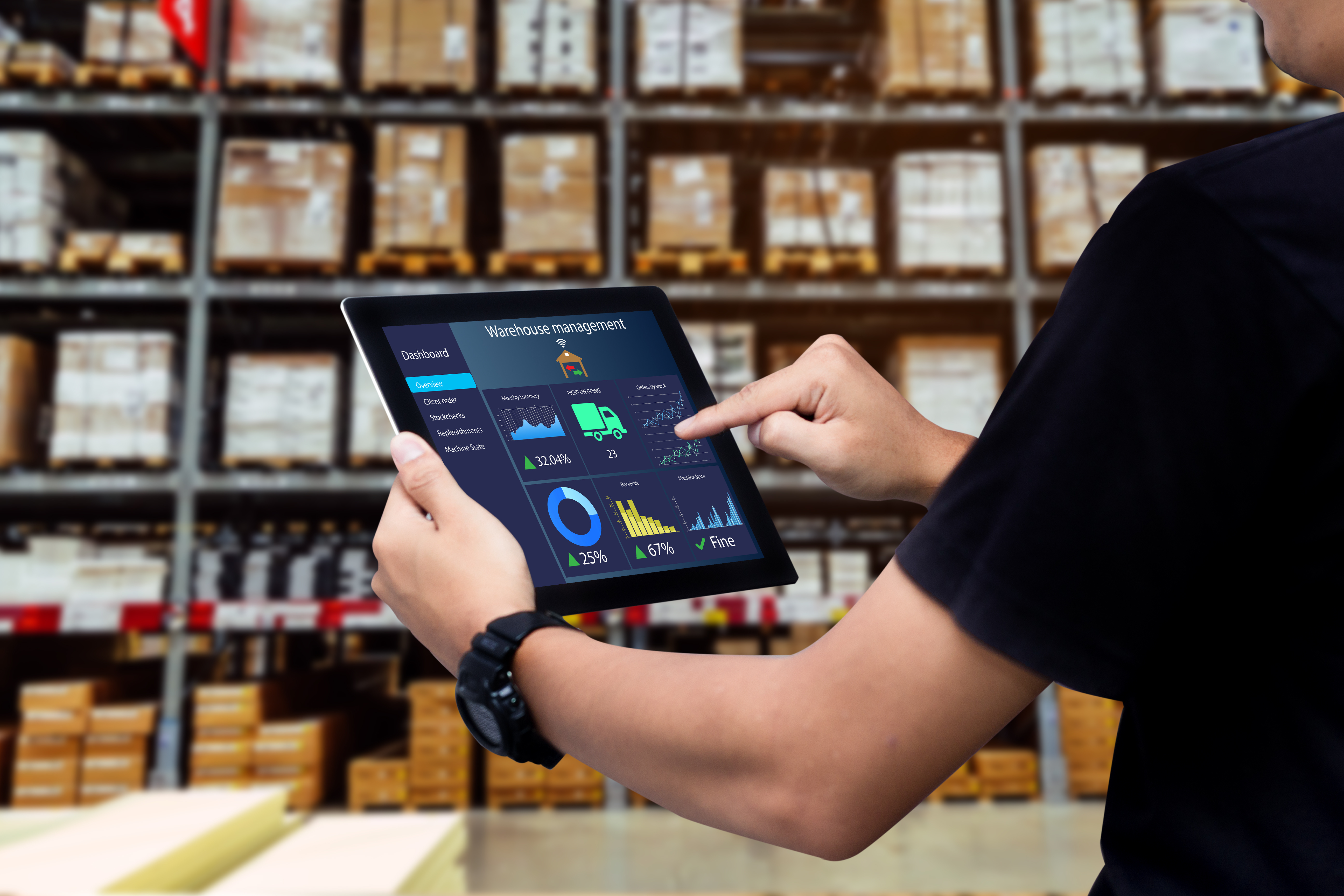 man monitoring warehouse inventory on an ipad