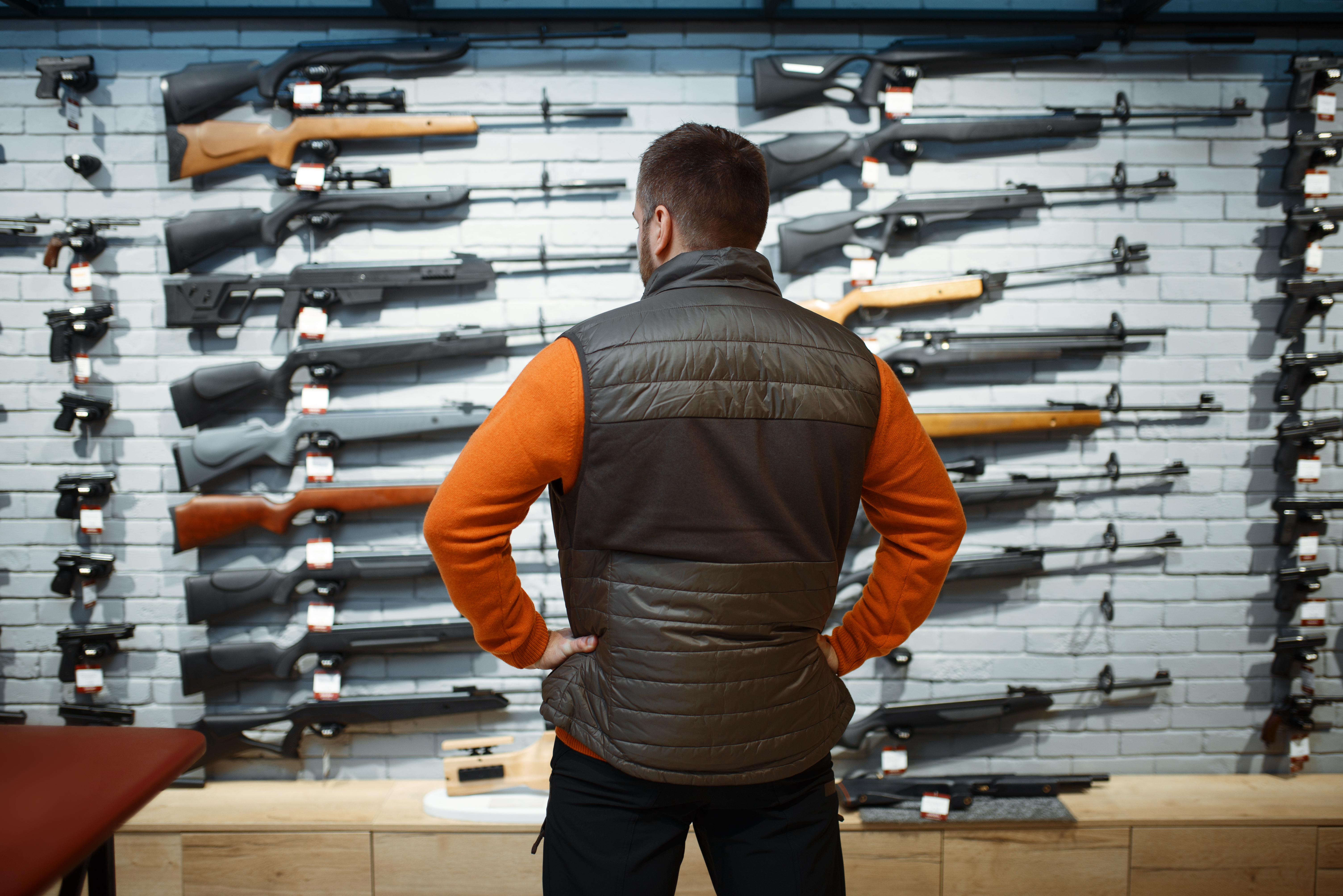 man looking at rifles in a store
